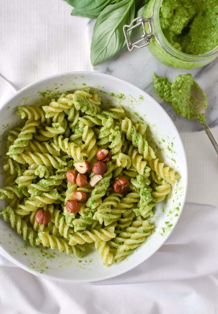 overhead shot of vegan pesto pasta with basil and pesto jar
