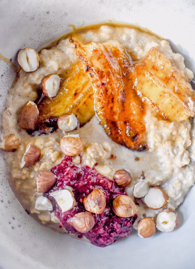 overhead close up shot of caramelised banana oatmeal with hazelnuts and chia jam