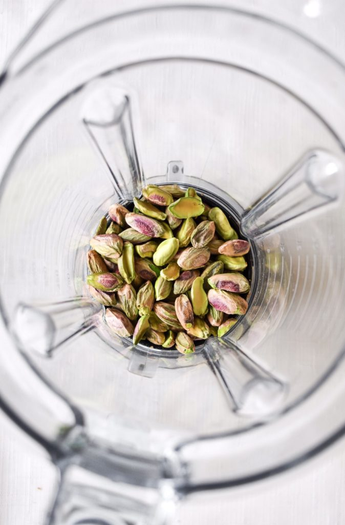 close up overhead shot of vitamix blender containing pistachios