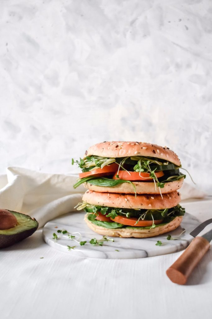 side shot of the ultimate vegan sandwich: a bagel bun with avocado, cucumber, tomato, cress + more!
