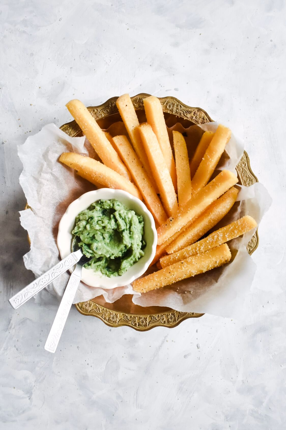 overhead shot of crispy polenta fries in a bowl with a bowl of avocado pesto