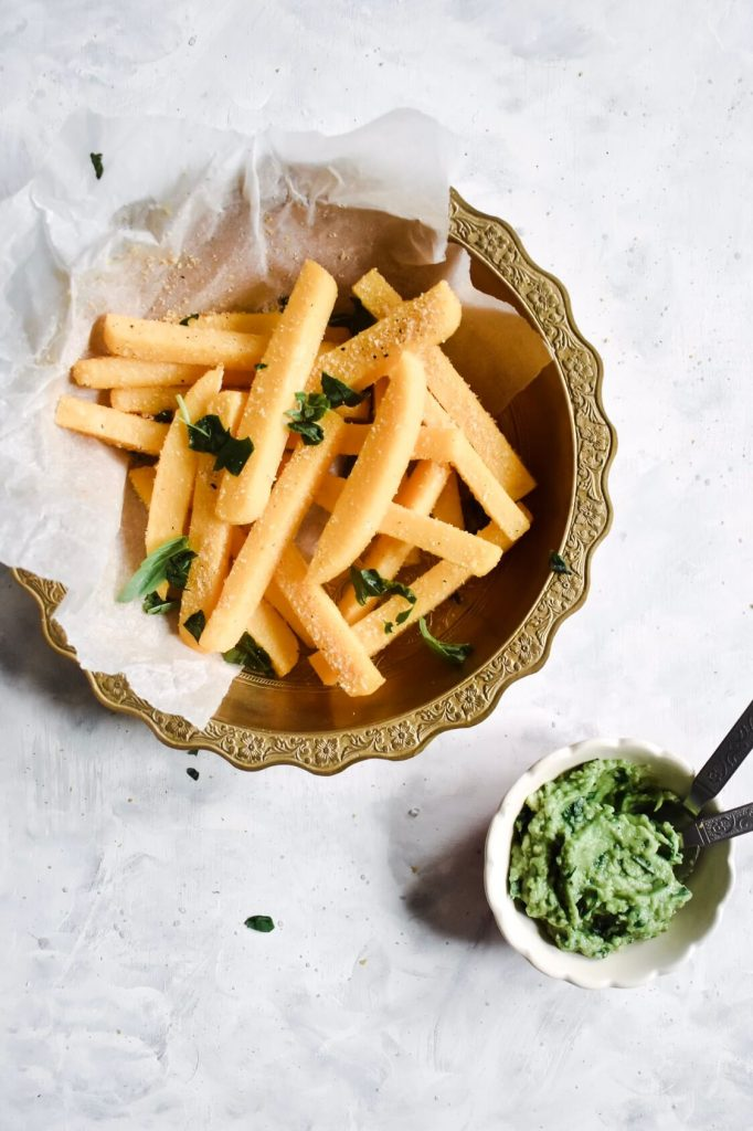 overhead shot of crispy polenta fries in a bowl with a bowl of avocado pesto on the side