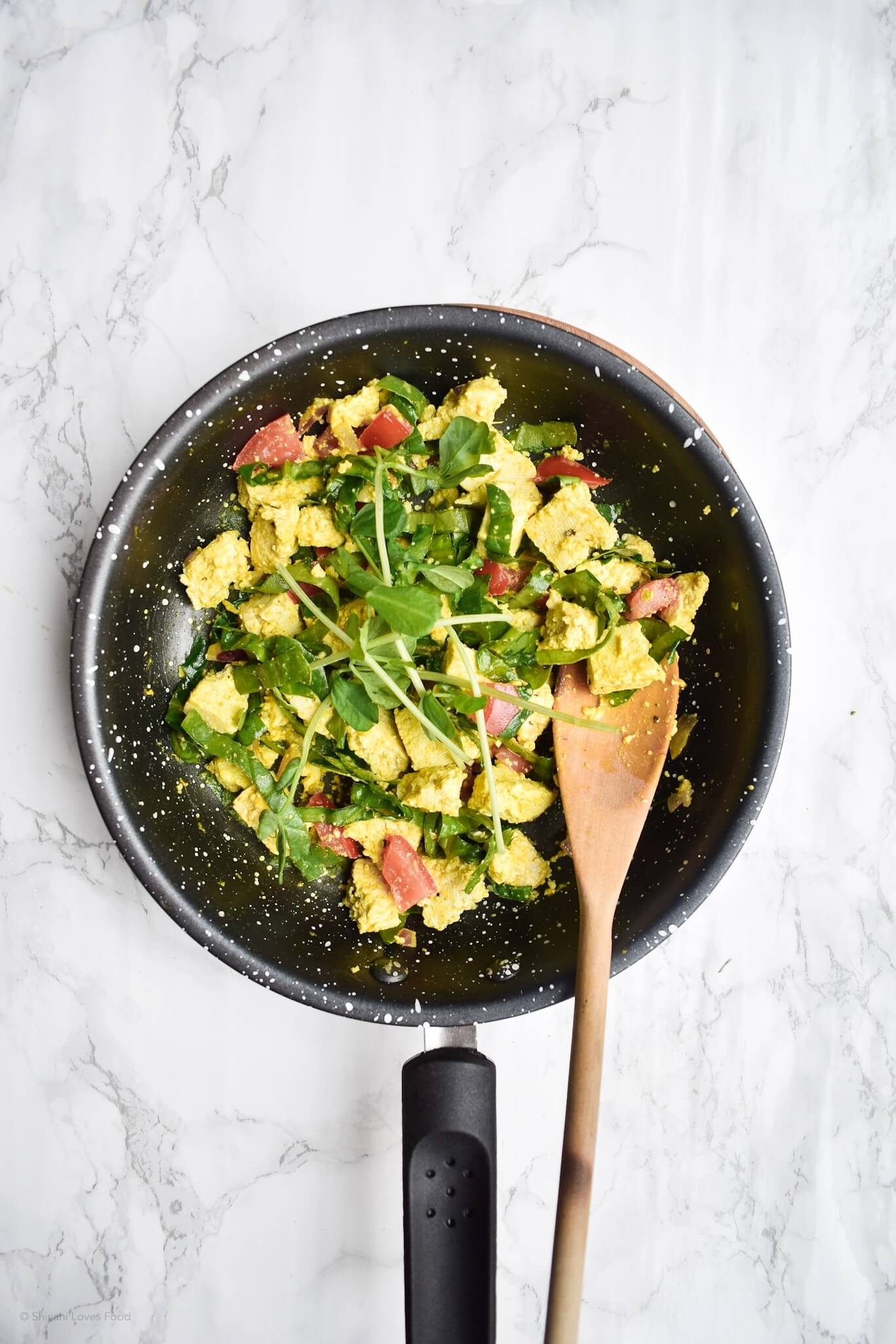 overhead photograph of scrambled tofu in a frying pan with a wooden spoon