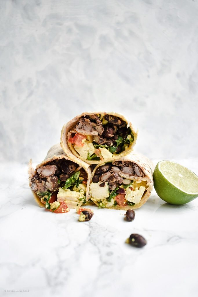 side photograph of breakfast burritos stacked on top of each other