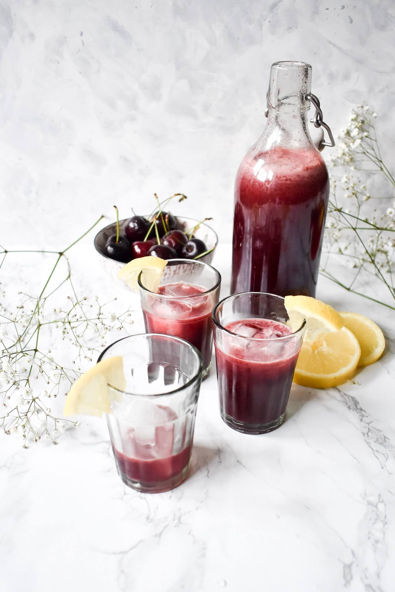 a photograph of 3 glasses of cherry lemonade and a glass bottle
