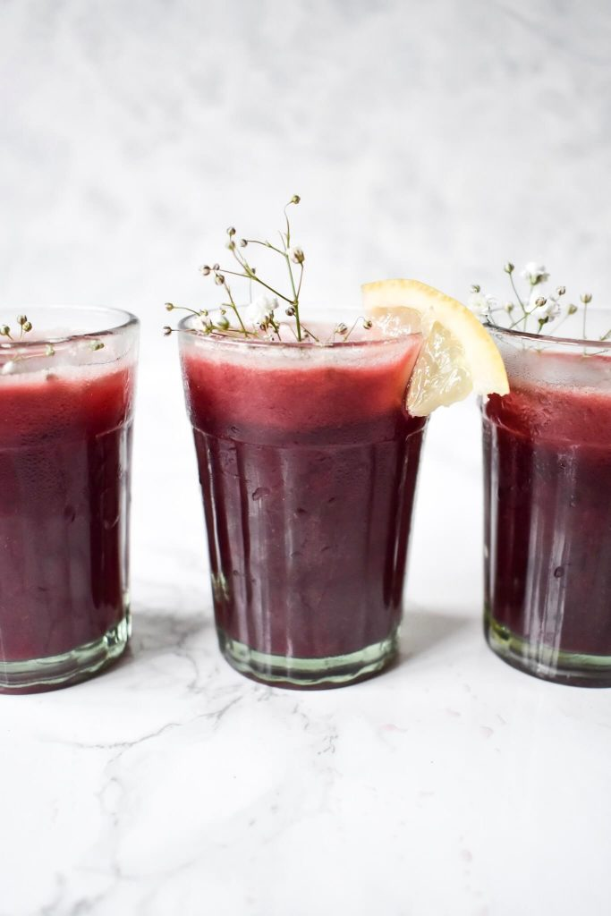 a side photograph of 3 glasses of cherry lemonade with a lemon wedge