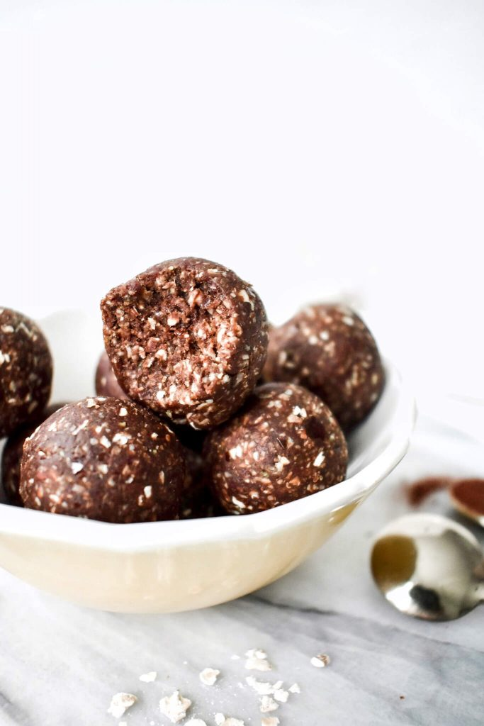 side photograph of some energy balls in a bowl, with a bite taken from one