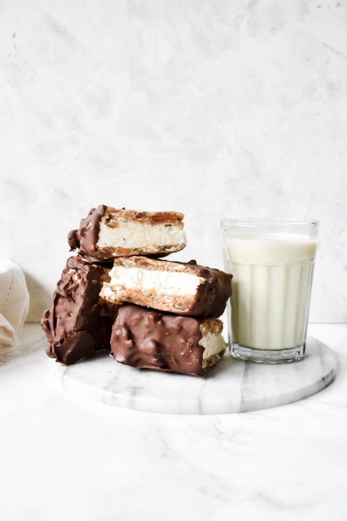 photograph of ice cream sandwiches stacked next to a glass of milk