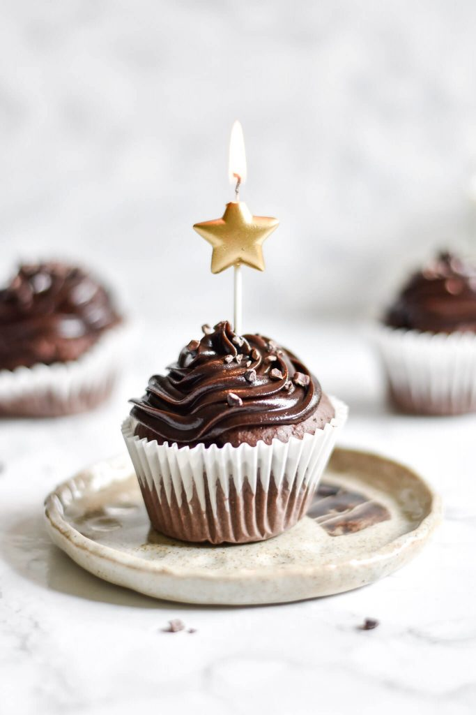side photograph of a cupcake with a candle in it