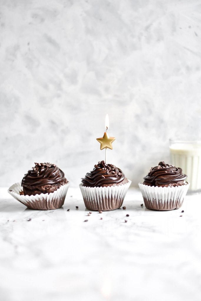 side photograph of three chocolate cupcakes and a candle