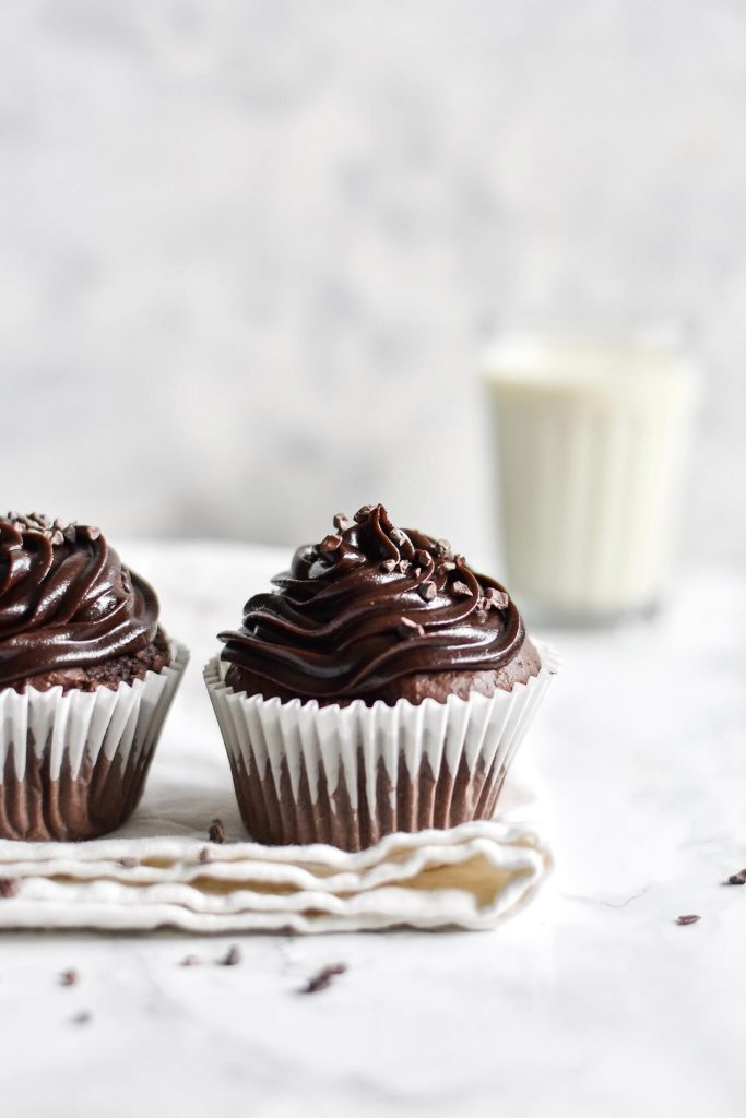 side photograph of two chocolate cupcakes topped with cacao nibs