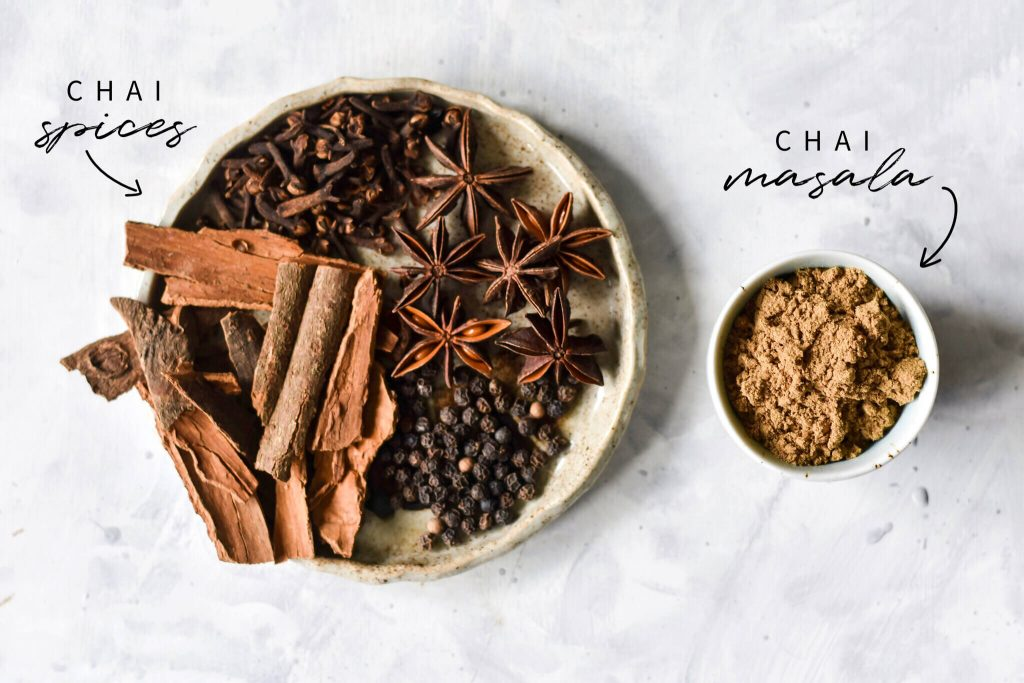 chai spices on a plate next to a small bowl of chai masala