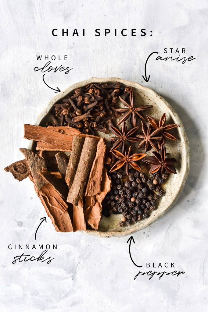 chai spices on a plate with text labels showing what the spices are: cloves, star anise, cinnamon and black pepper