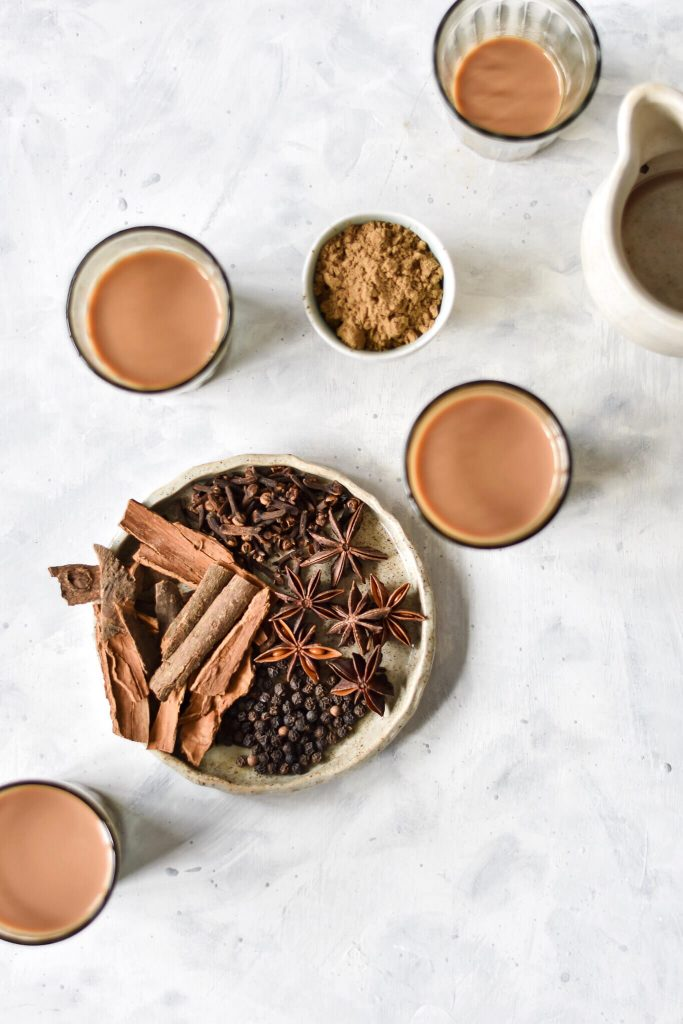 a flatlay showing cups of chai, a plate of spices, and a small bowl of chai masala