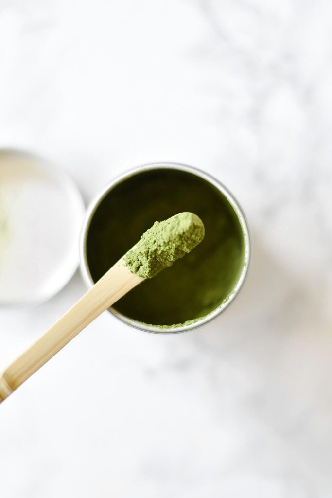 close up photograph of matcha powder on a scoop