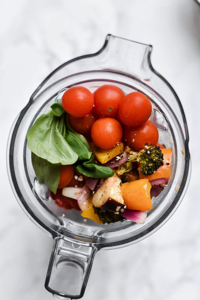 a blender filled with roasted vegetables, cherry tomatoes, basil and spices