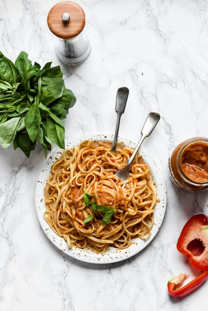 flat lay of hidden vegetable pasta sauce, pasta, basil and a pepper