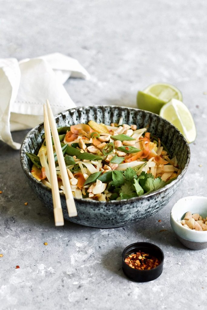 a bowl of pad thai with some chopsticks
