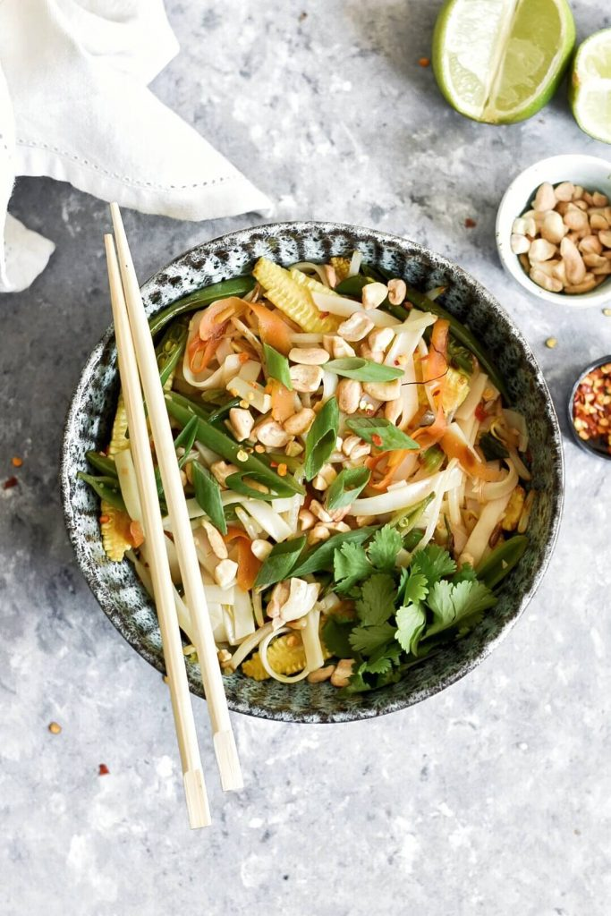 a bowl of pad thai topped with spring onions and peanuts