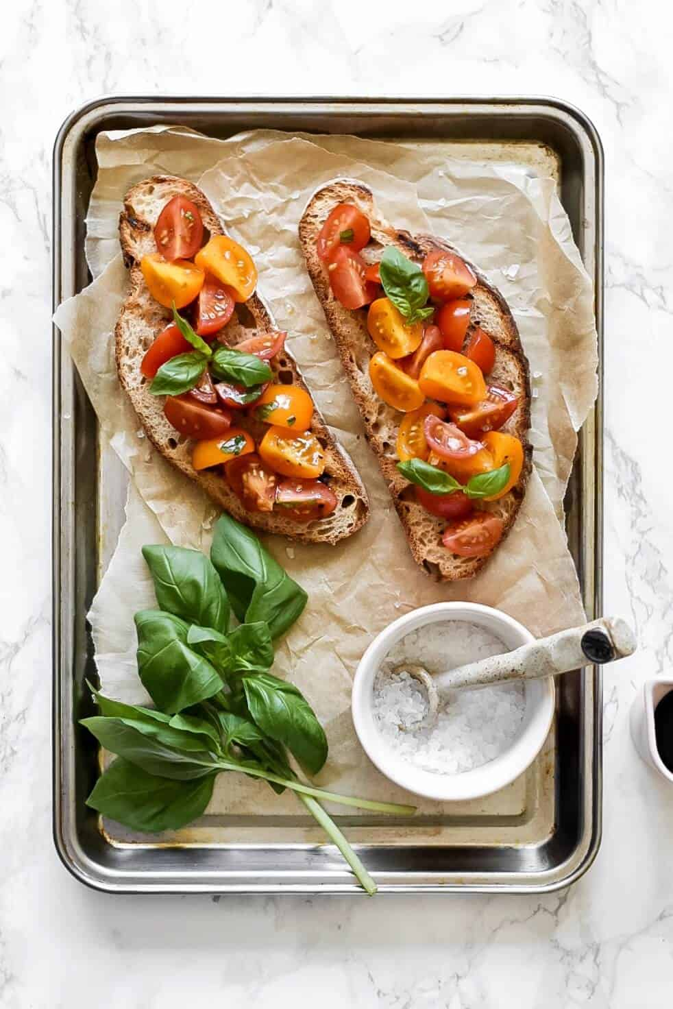 2 slices of bruschetta on a tray with basil and salt
