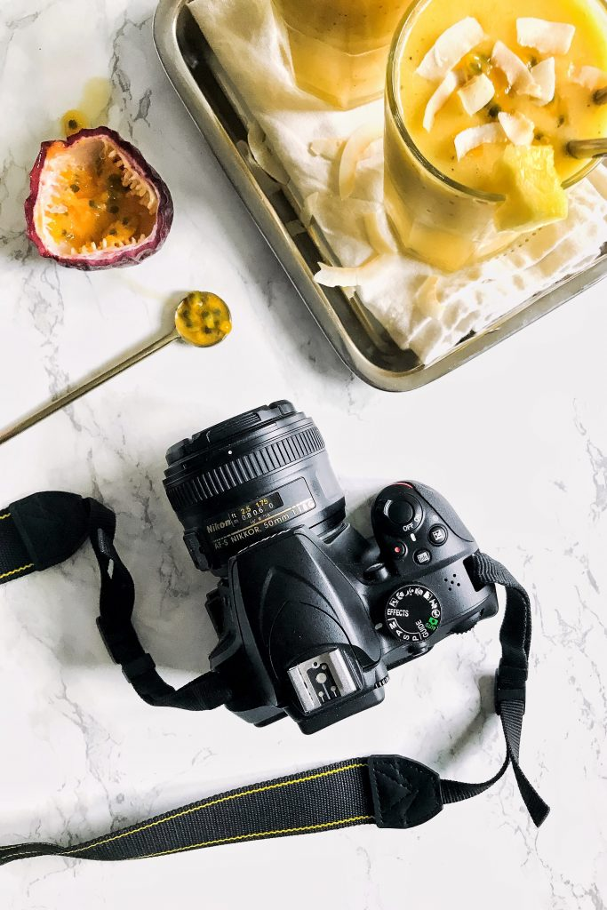 a DSLR camera next to some smoothies