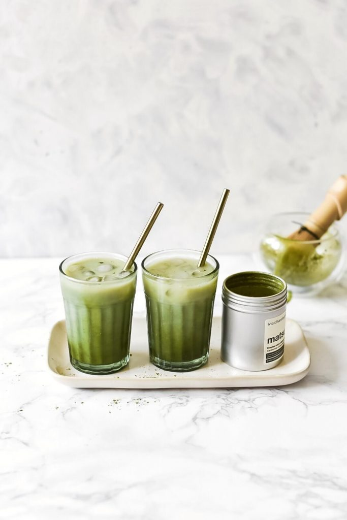 two iced matcha lattes next to a pot of matcha