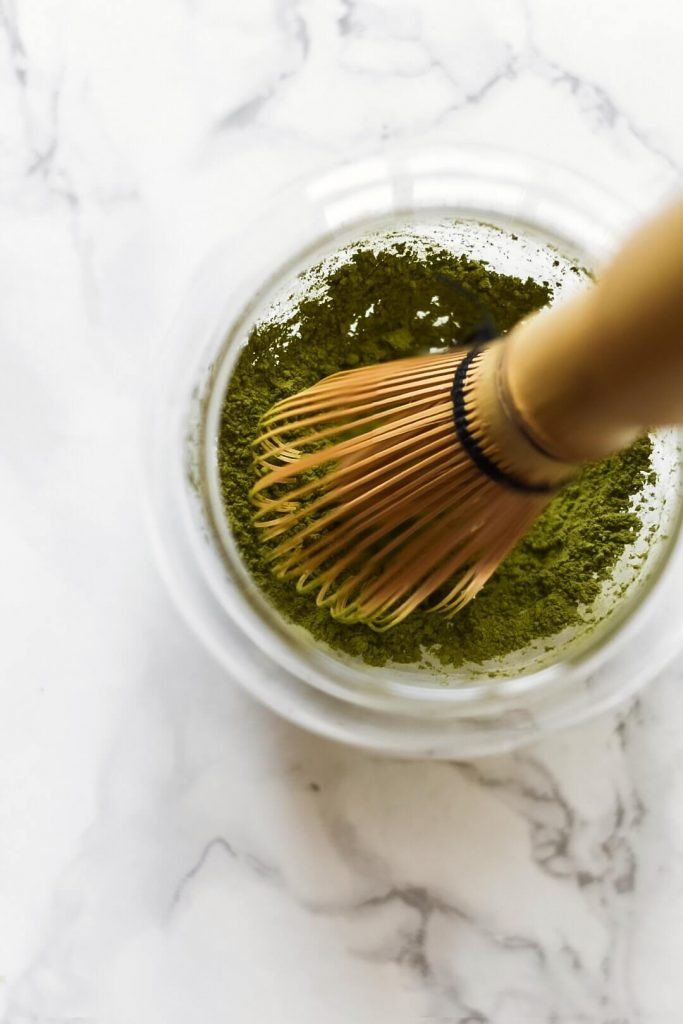 matcha whisk in a bowl with matcha powder