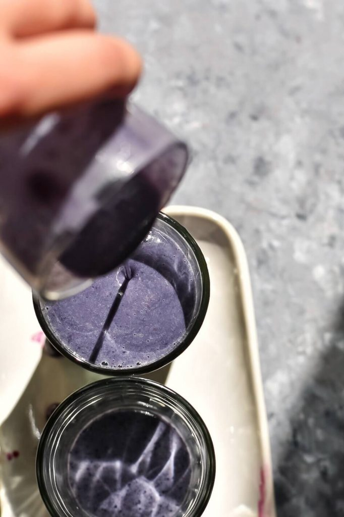 blueberry almond butter smoothie being poured into a glass