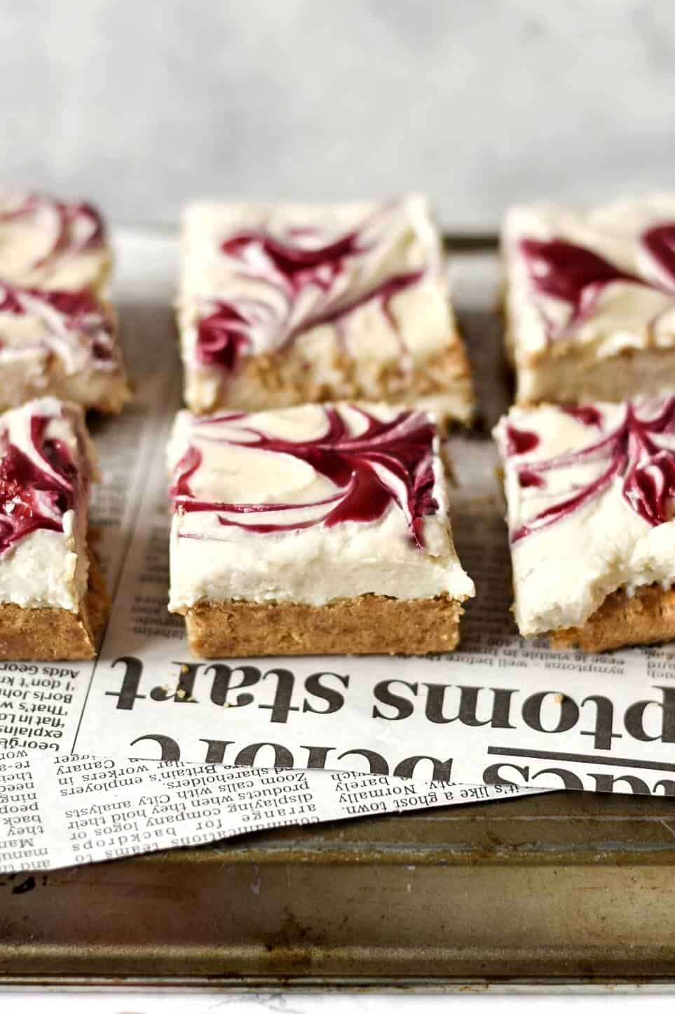 a side view of vegan cheesecake bars swirled with strawberry sauce