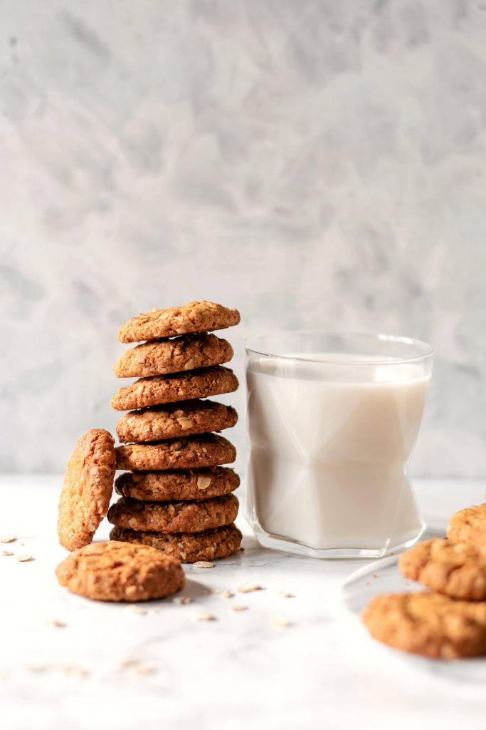 a stack of oat cookies next to a glass of milk