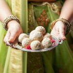 a person holding a plate of coconut ladoos