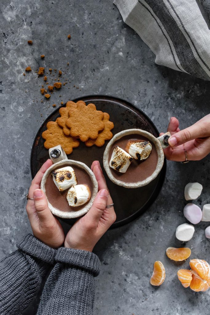 two mugs of orange hot chocolate topped with marshmallows
